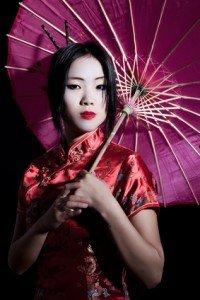 Frau im Rotem Kimono mit einem Lilanem Schirm. Schlichte Kimono Muster sind zu sehen.