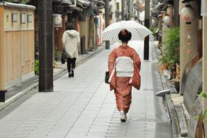 Frau im rotem Kimono mit großem weißen Obi auf Japanischer Straße