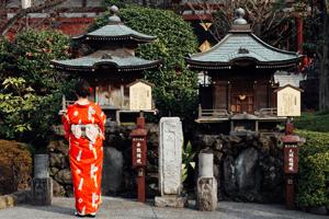 Kimono Tradition - Frau im rot-orangen Kimono vor einem Schrein.