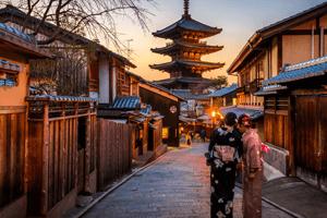Frauen im Kimono auf japanischer Straße. In der Bildmitte im hintergrund ist ein Japanischer Schrein zu sehen.