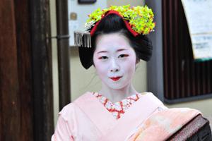 Geisha Kimono in Pink mit grünem Haarschmuck lächelnd
