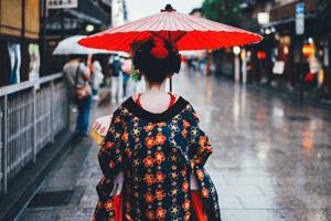 Geisha Kimono mit Rotem Schirm von hinten auf der Straße