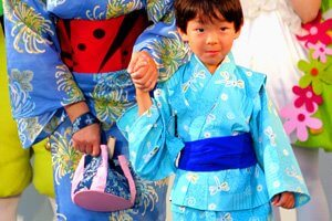 Kimono mit Libellen muster getragen von einem kleinen Jungen. Er hällt die Hand seiner Mutter.