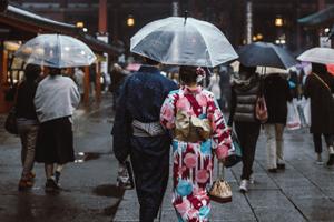 Paar in Kimono unter transparentem Regenschirm von hinten.