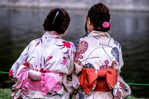 Zwei Frauen im Kimono mit Obi schleifen von hinten