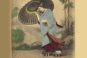 Altes Foto auf dem jemand mit einem Kimono, Geta und Regenschirm zu sehen ist.