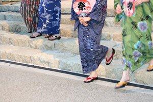 Drei frauen im Kimono die eine Treppe runterlaufen.