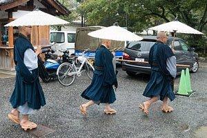 Drei Mönsche mit Regenschirmen die nach rechts laufen.
