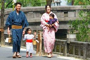 Eine Familie die lächelnd spaziert. Links ist der Vater, rechts die Mutter und in der mitte die Tochter.