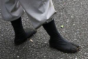 Japanische Fußbekleidung, schwarze Tabi getragen auf der straße.
