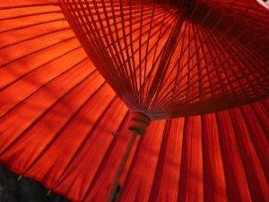 Roter Regenschirm. Rangezoomt an die vielen holzstreben.