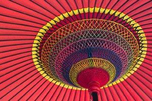 Roter Regenschirm mit schwarzem stiel. Dekoriert mit bunten ringen am Kopfstück des Regenschirms.