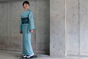 Frau im Blauen Iro Muji Kimono vor einer Steinwand.