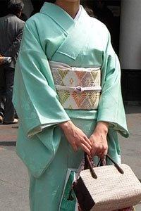 Frau in Türkis Iro Muji Kimono mit Handtasche.