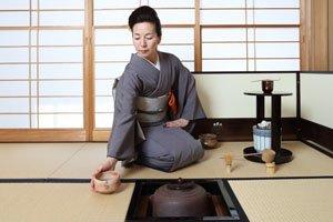 Frau mit einem Iro Muji Kimono bei einer Teezeremonie.