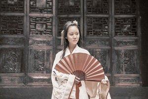 Frau vor einer verzierten Tür im Kimono. Sie trägt einen Sensu Handfächer.