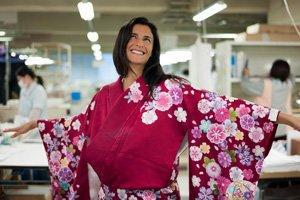 Eine Frau im rosa Kimono mit Blumen Motiven. Sie lächelt und schaut nach oben.