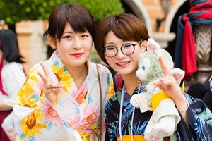 zwei frauen im Kimono. Dsie zeigen das Peace Zeichen mit den fingern. Die linke hat eine runde brille an und hält einen Grauen Teddy Bear in der Hand.