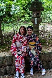 Zwei Frauen sitzen auf steinen. Sie haben beide einen Kimono an. Die linke ist in pink und die rechte in dunkelblau.
