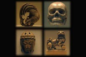 Vier verschiedene Netsukes. Eine Eule, ein Menschlicher Schädel, eine Maske und ein Tempelwächter Löwe.
