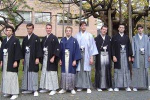 Eine Gruppe von jungen männern vor einer art schule mit traditionellen Kimonos und Haori.